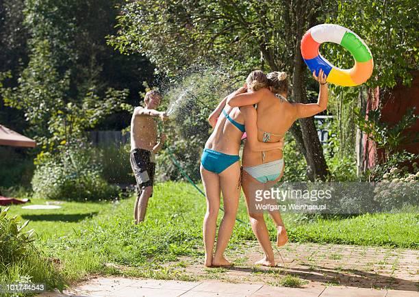 Austria, Salzburger Land, Teenagers (14-15) having fun with garden hose