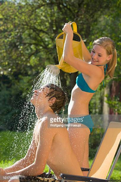 Austria, Salzburger Land, Teenagers (14-15) in garden, Teenage boy getting a shower