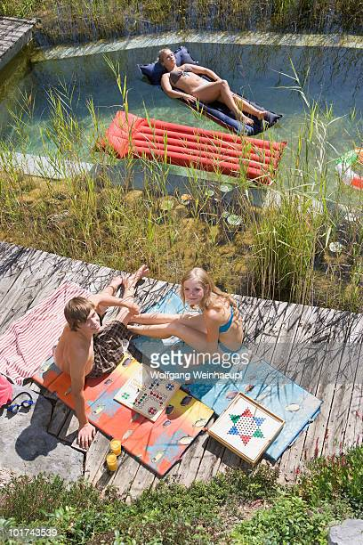 Austria, Salzburger Land, Teenagers (14-15) relaxing at garden pool, elevated view