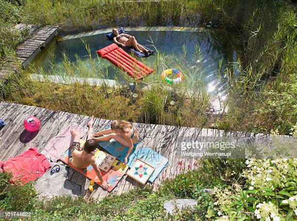 Austria, Salzburger Land, Teenagers (14-15) relaxing on pool in garden, elevated view