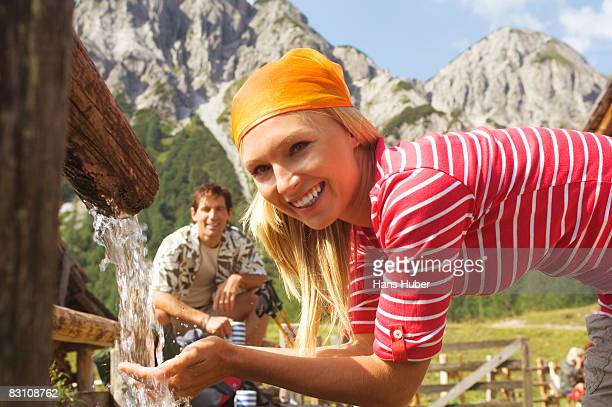 Austria, Salzburger Land, Woman drinking water from fountain, man sitting in background, smiling, portrait