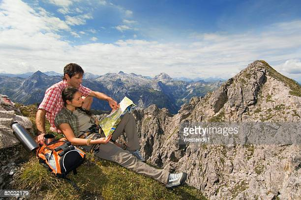 Austria, Salzburger Land, young couple looking at map on mountain top