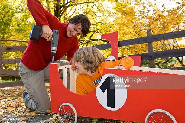 Austria, Salzburger Land, Young man fixing soapbox car, boy (12-13) watching