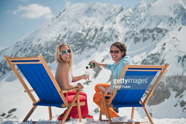 Austria, Salzburger Land, Young man pouring champagne for woman in deckchair, portrait