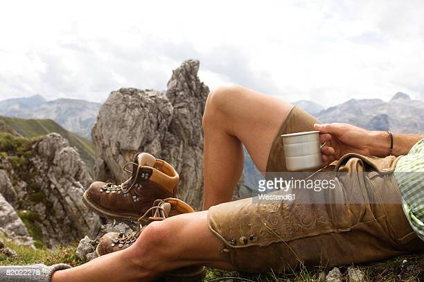 Austria, Salzburger Land, man lying on mountain holding mug