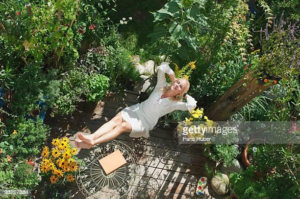 austria, salzburger land, young woman in garden, relaxing, elevated view - hausgarten stock-fotos und bilder