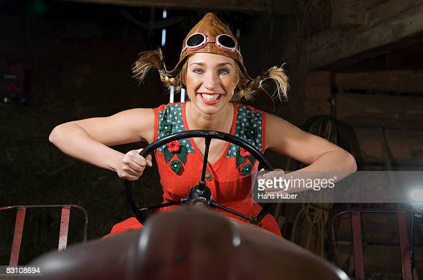Austria, Salzburger Land, young woman on tractor holding steering wheel, smiling, portrait