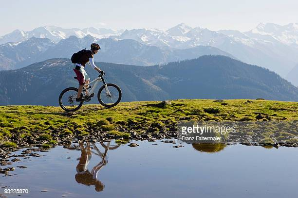 Austria, Salzburger Land, Zell am See, Woman mountain biking, side view