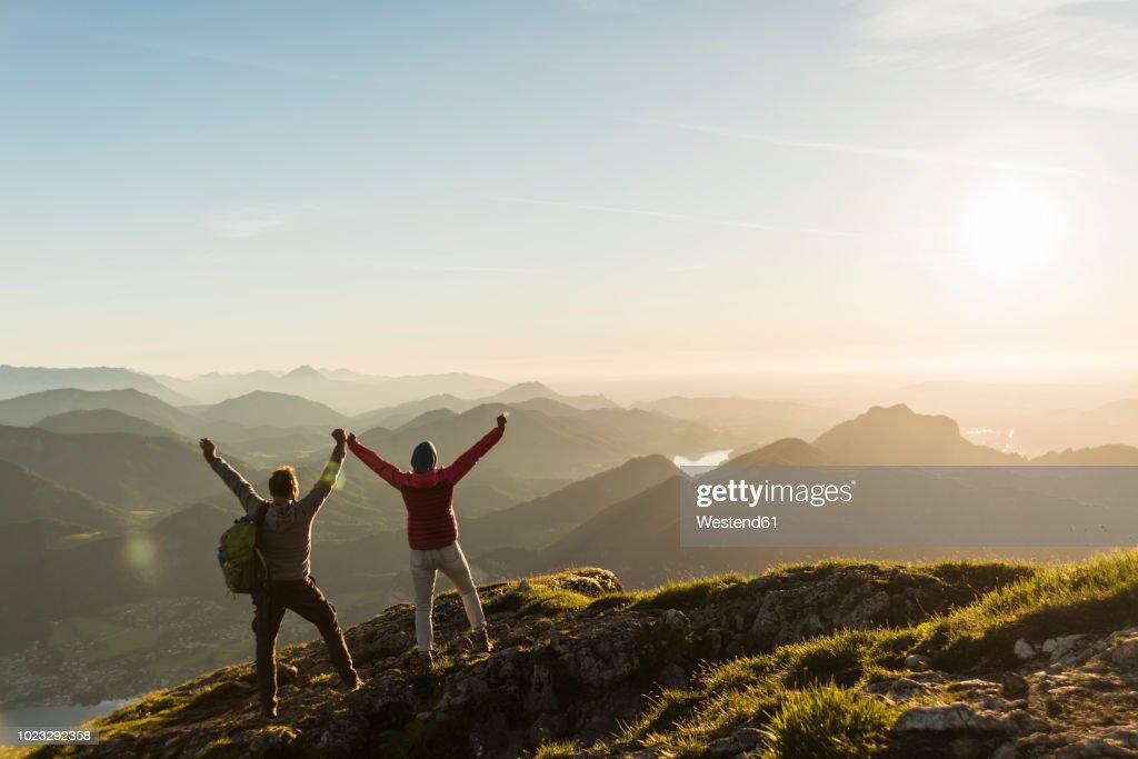 Austria, Salzkammergut, Cheering couple reaching mountain summit : Stock-Foto