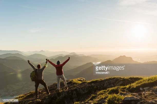 austria, salzkammergut, cheering couple reaching mountain summit - éxito fotografías e imágenes de stock