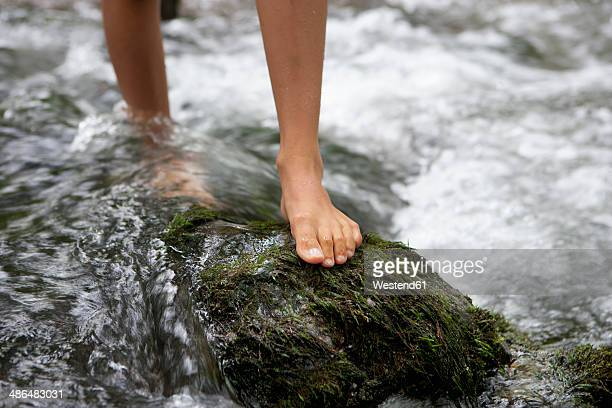 Austria, Salzkammergut, Mondsee, feet of teenage girl crossing a brook