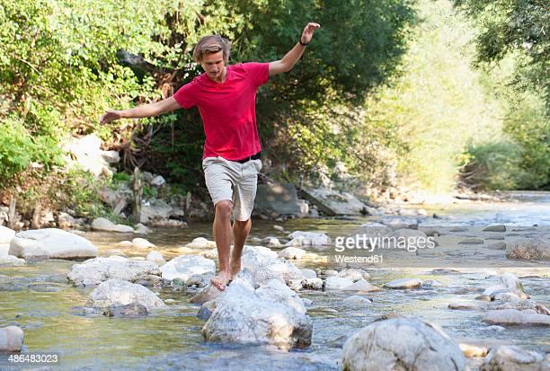 Austria, Salzkammergut, Mondsee, young man crossing a brook