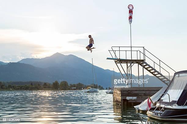 austria, sankt wolfgang, man jumping from platform into lake - diving platform stock pictures, royalty-free photos & images