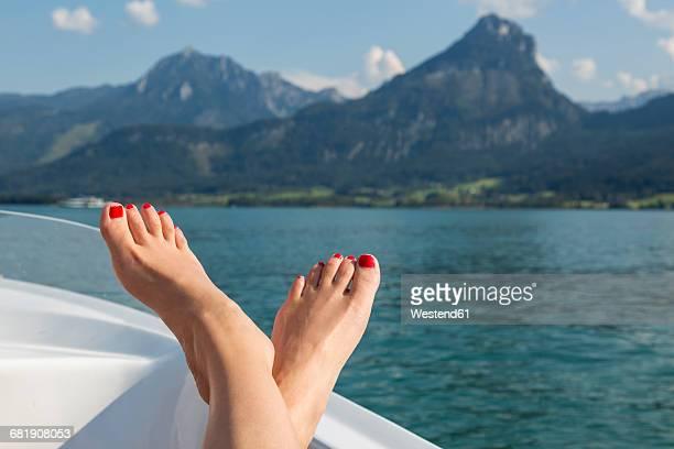 Austria, Sankt Wolfgang, woman's feet on boat in lake