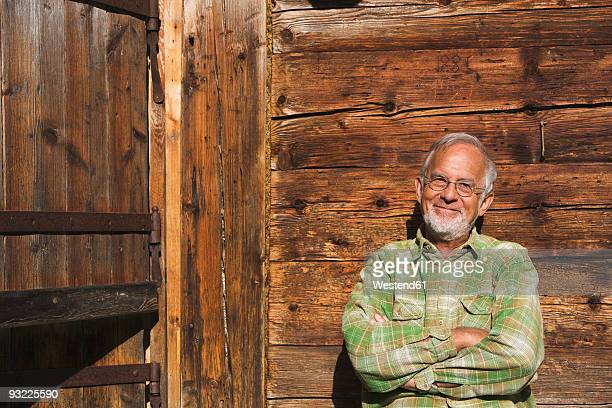 Austria, Senior man leaning against wooden wall, arms crossed, portrait