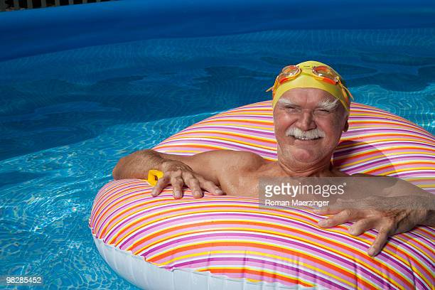 Austria, Senior man with floating tire in swimming pool, smiling, portrait