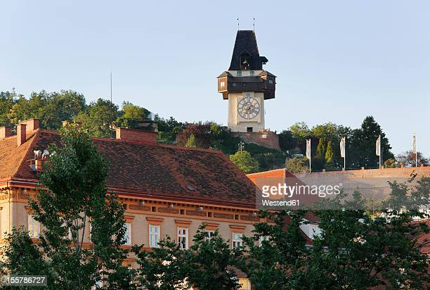 austria, styria, graz, view of clock tower on schlossberg hill - graz stock photos and pictures