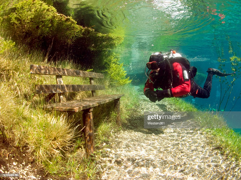Austria, Styria, Tragoess, lake Gruener See, diver in front of a park bench : Stock Photo