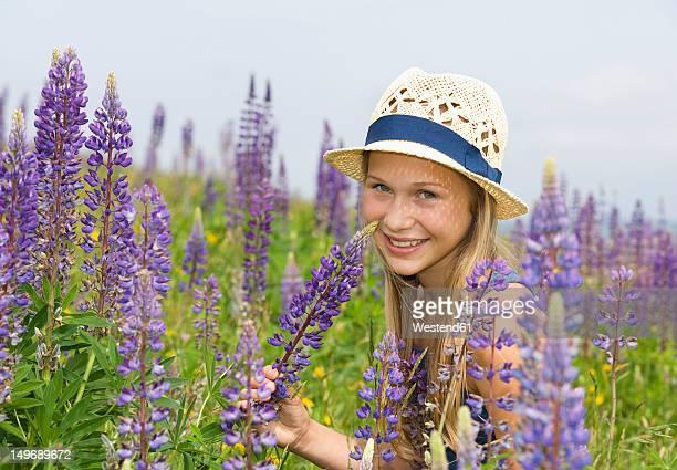 Austria, Teenage girl holding lupine flower, smiling, portrait