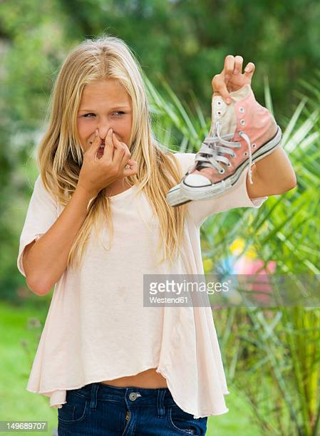 Austria, Teenage girl holding sneakers