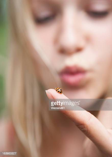 Austria, Teenage girl looking at ladybird on her finger