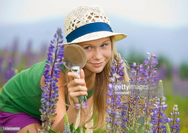 Austria, Teenage girl looking at lupine through magnifying glass
