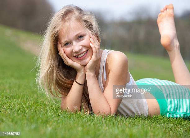 Austria, Teenage girl lying on meadow, smiling, portrait