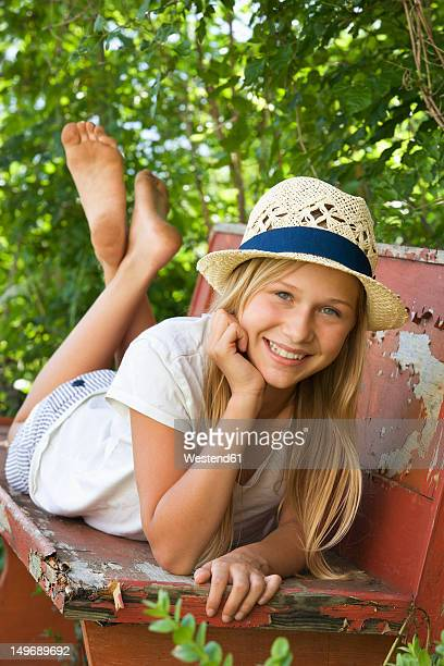 Austria, Teenage girl relaxing on bench in garden, portrait