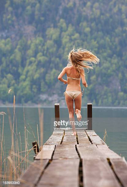 Austria, Teenage girl running on jetty
