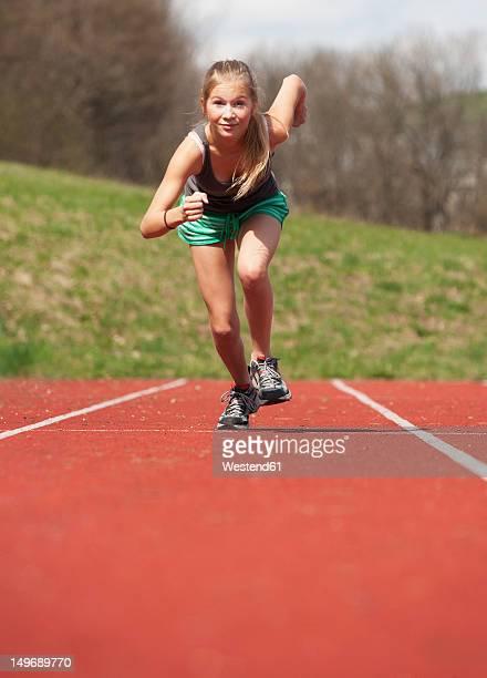 austria, teenage girl running on track, portrait - one teenage girl only stock pictures, royalty-free photos & images