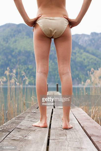 austria, teenage girl standing on jetty - tienermeisjes stockfoto's en -beelden