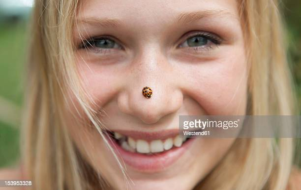 Austria, Teenage girl with ladybird on her nose, smiling, portrait