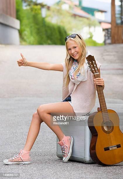 Austria, Teenage girl with wheeled luggage and guitar, portrait