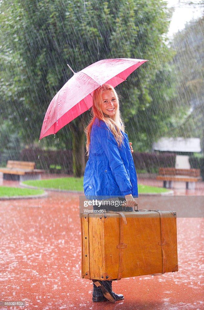 austria thalgau teenage girl with red umbrella standing in the rain