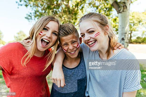 austria, three teenagers with national colors painted on their cheeks celebrating together - austrian culture stock pictures, royalty-free photos & images