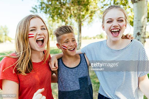 Austria, three teenagers with national colors painted on their cheeks celebrating together