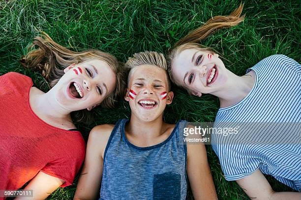 Austria, three teenagers with national colors painted on their cheeks lying on a meadow