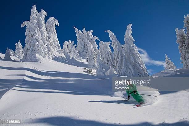 austria, tirol, kitzbuehel, man doing telemark skiing - kitzbühel stock pictures, royalty-free photos & images