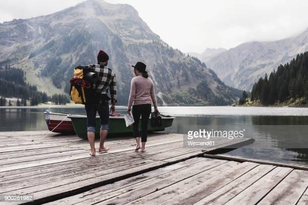 Austria, Tyrol, Alps, couple walking on jetty at mountain lake