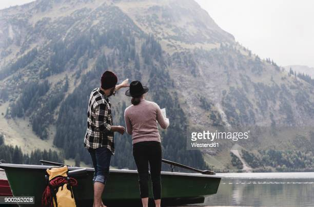 Austria, Tyrol, Alps, couple with map standing at mountain lake