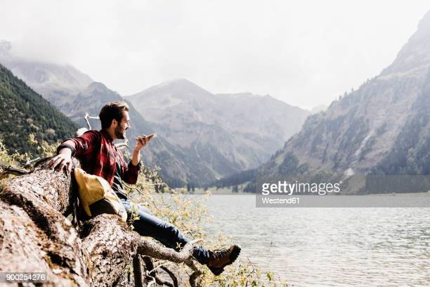 Austria, Tyrol, Alps, hiker on tree trunk at mountain lake using cell phone