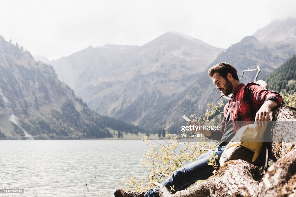 Austria, Tyrol, Alps, hiker relaxing on tree trunk at mountain lake checking cell phone : Stock Photo