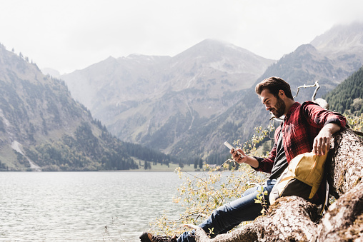 Austria, Tyrol, Alps, hiker relaxing on tree trunk at mountain lake checking cell phone - gettyimageskorea