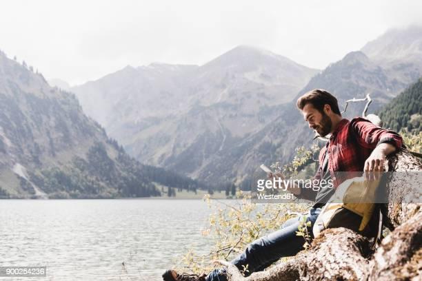 austria, tyrol, alps, hiker relaxing on tree trunk at mountain lake checking cell phone - ein mann allein stock-fotos und bilder