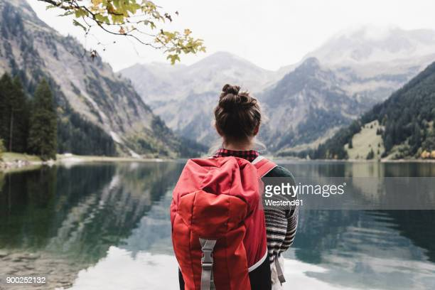 austria, tyrol, alps, hiker standing at mountain lake - rucksacktourist stock-fotos und bilder
