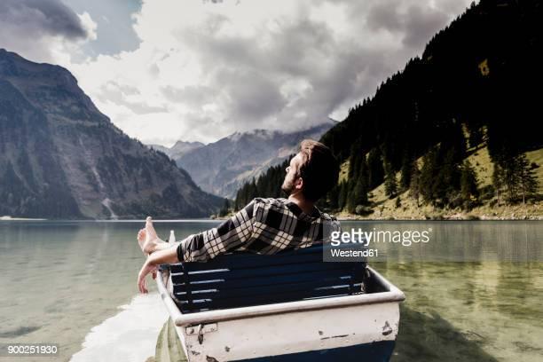austria, tyrol, alps, relaxed man in boat on mountain lake - alles hinter sich lassen stock-fotos und bilder