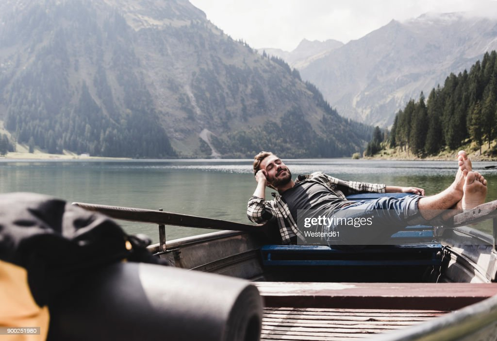 Austria, Tyrol, Alps, relaxed man in boat on mountain lake : Stock-Foto