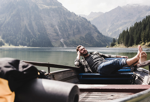 Austria, Tyrol, Alps, relaxed man in boat on mountain lake - gettyimageskorea