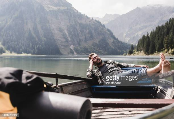 austria, tyrol, alps, relaxed man in boat on mountain lake - freizeitaktivität stock-fotos und bilder