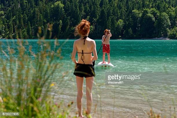 austria, tyrol ammergau alps, plansee, teenage boy standing on paddleboard, sister waiting on lakeshore - seeufer stock-fotos und bilder